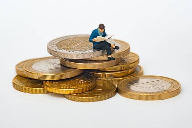 איש יושב על מטבעות גדולים - דוגמה לכסף גדול